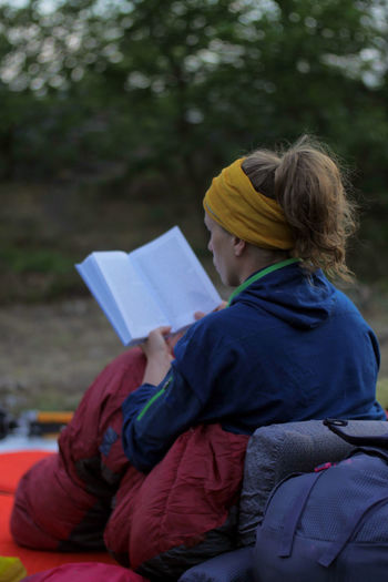 young caucasian female reading book while outdoor camping Backpacking Camping Hiking Nature Reading Travel Trekking Woman Activity Adult Book Casual Clothing Caucasian Day Education Female Focus On Foreground Girl Hikingadventures Hobby Holding Learning Leisure Activity Lifestyles One Person Outdoors Paper People person Publication Reading Real People Relaxation Sitting Studying Teenager Tent Three Quarter Length Vacation Warm Clothing Women