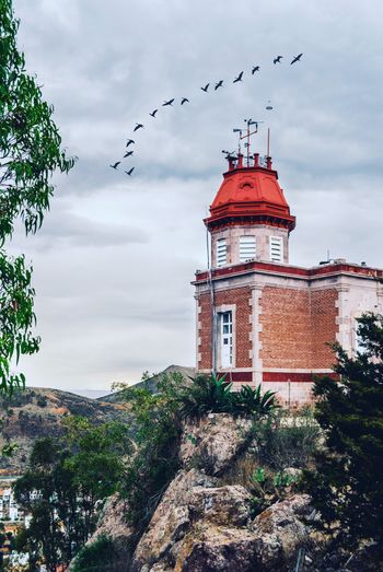 Low angle view of birds flying over lighthouse against sky