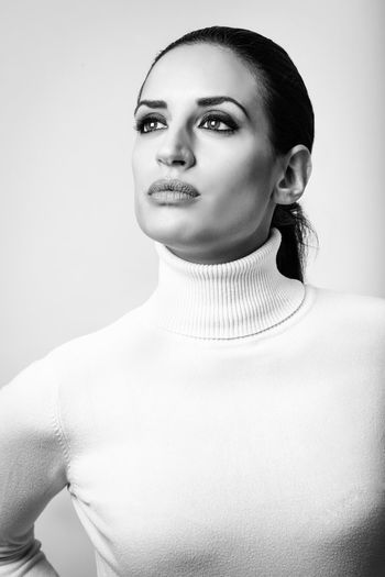 Close-Up Of Woman Wearing Turtleneck Against White Background