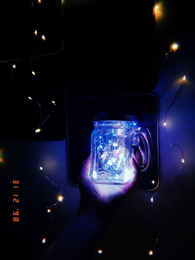 Man photographing illuminated smart phone at night