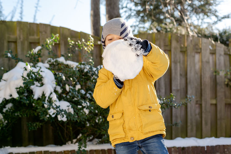 Little boy plays with snow in the backyard.