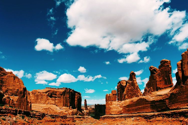 Low angle view of rock formations at arches national park against cloudy blue sky