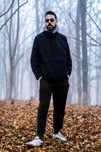 Full length of young man standing in forest during winter
