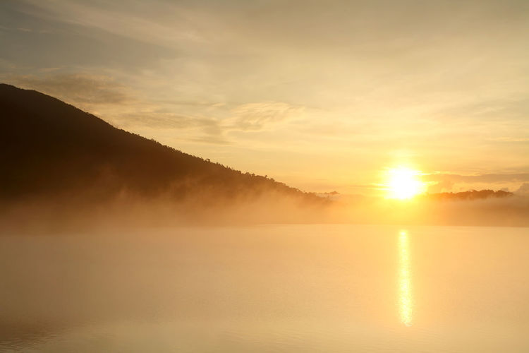 Beautiful landscape with fog and mountain at water dam in the during the sunrise of Thailand Sunset Tranquility Sky Scenics - Nature Tranquil Scene Water Beauty In Nature Sun Idyllic Lake Cloud - Sky Reflection No People Nature Sunlight Fog Mountain Outdoors Sunrise