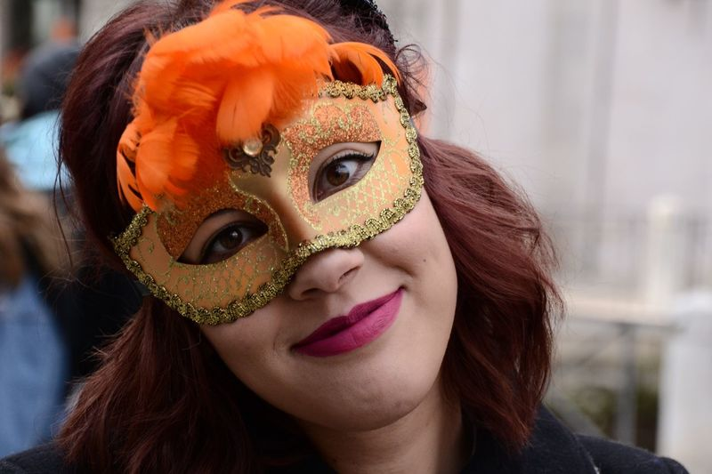 Portrait of woman wearing orange masquerade mask