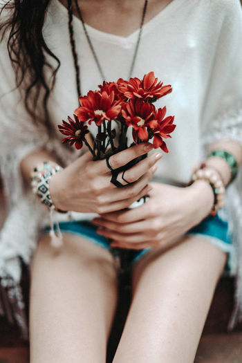 Hippie female hands holding a bouquet of wild red flowers