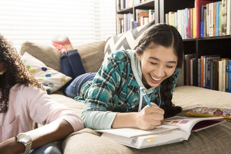 Happy girl sitting on book