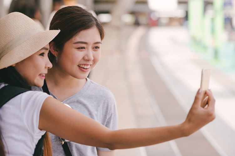 Female Friends Taking Selfie While Standing On Footpath