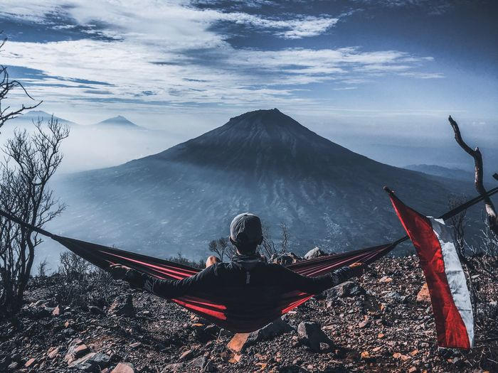 Rear view of man sitting on hammock against mountain