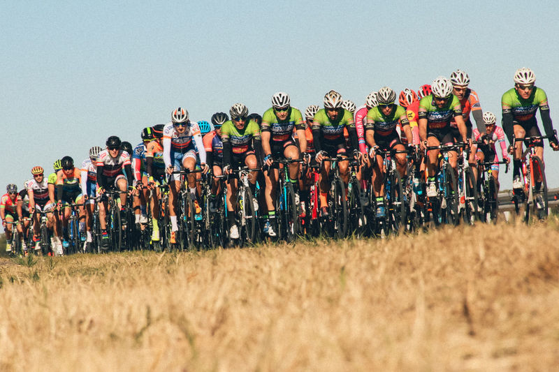 Cyclists Riding Bicycles On Grassy Field Against Clear Sky