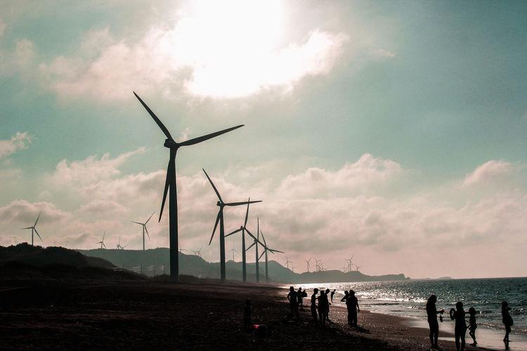 People with wind turbines on beach against sky