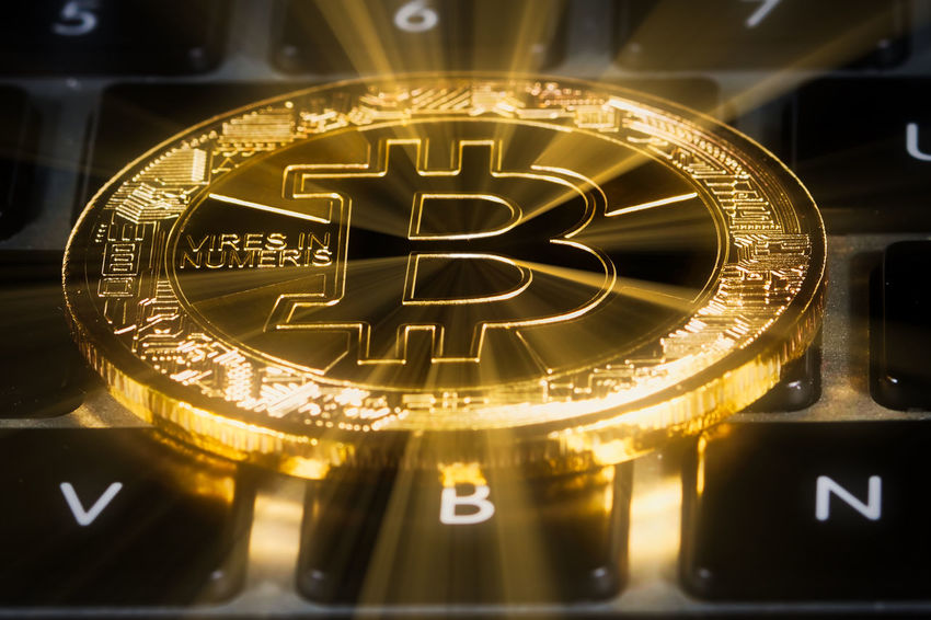 Bitcoin positioned on top of keyboard. Physical coin used to illustrate cryptocurrency and blockchain technology. Currency Bitcoin Blockchain Blockchain Technology Close-up Coin Computer Concept Cryptocurrency Digital Gold Colored Investment Keyboard Technology