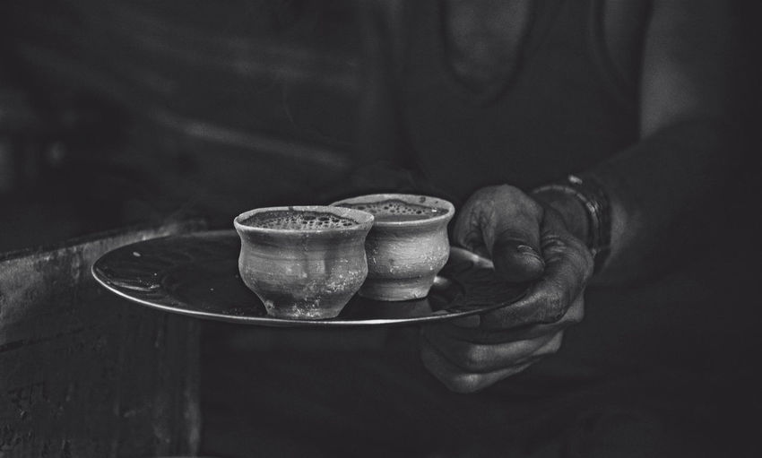Midsection of man serving tea in mud cup on plate