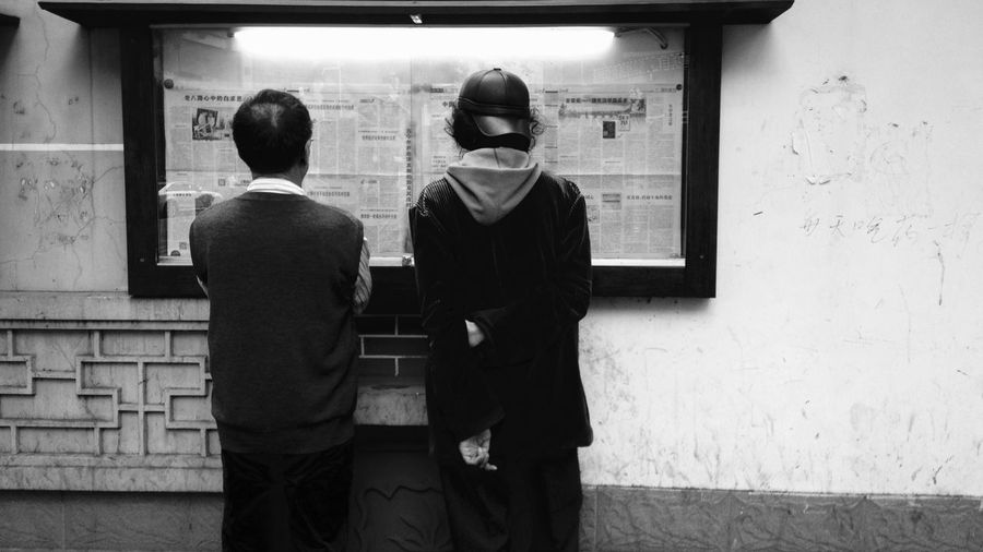 Rear view of men reading newspaper in cabinet on wall