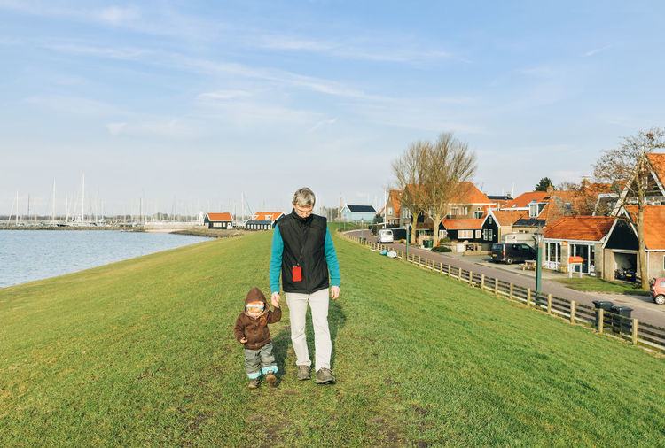 Man with toddler walking on dyke – Hindeloopen, Netherlands, Europe Grandfather Granddaughter Grandchild Generations Multi-generation Family Walking Hiking Wanderlust Hikingadventures Netherlands Vacations Offspring Two People Child Childhood Toddler  Toddlerlife First Steps Dyke  Friesland Front View Holding Hands Togetherness Bonding Ijsselmeer Grass Real People Water Full Length Sky Nature Leisure Activity Day Lifestyles Outdoors 17.62°