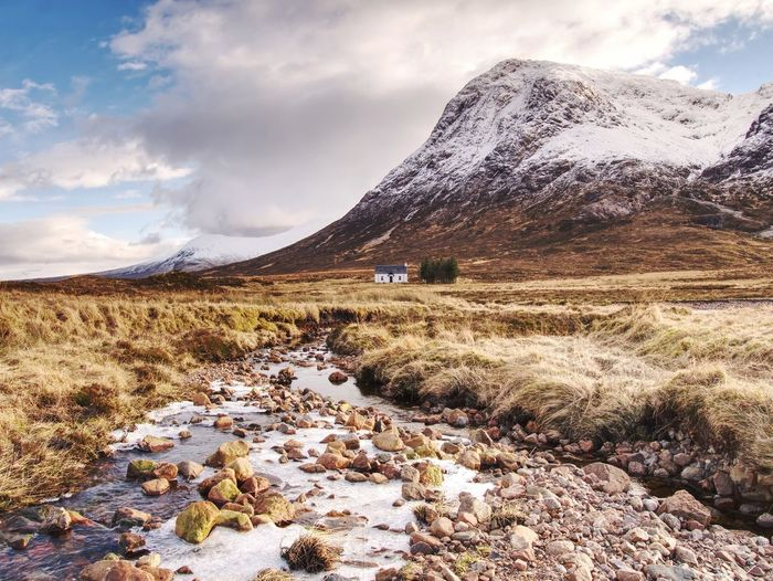 River at base of snowy mountains in scottish highlands near glencoe in winter. cold winter morning