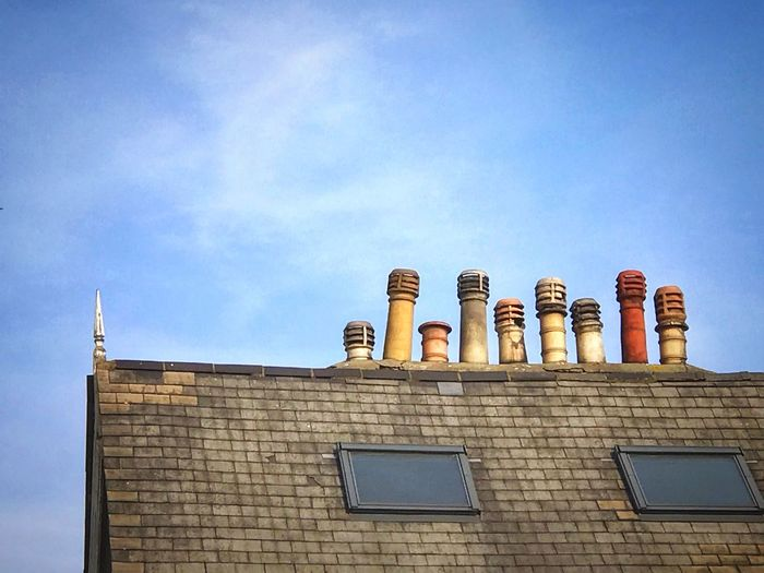 Low angle view of roof with chimneys against sky