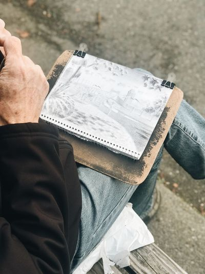 Low section of man with painting sitting outdoors