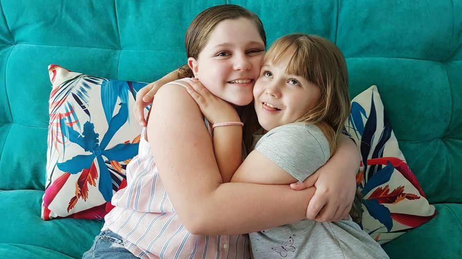 Portrait of cute overweight girl embracing sister at home