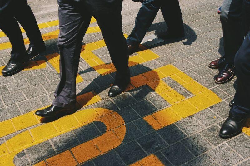 Low section of businessmen walking on street