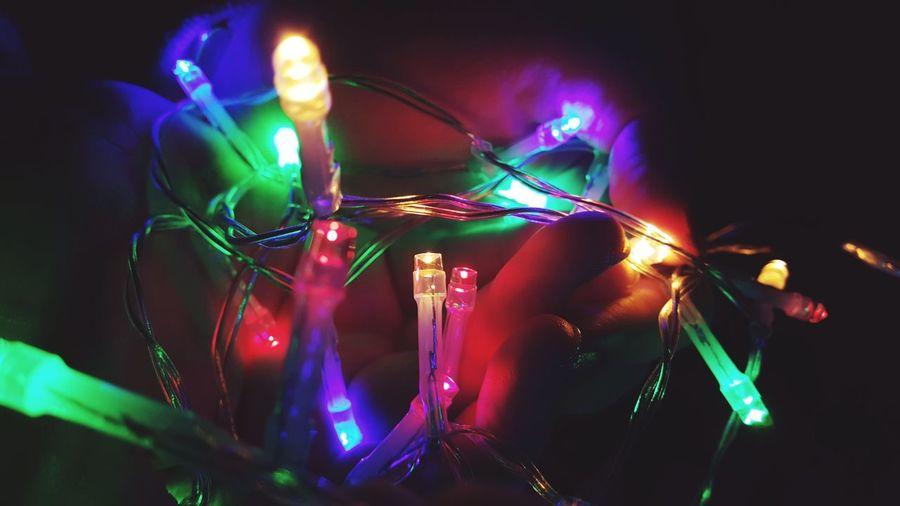 Close-Up Of Human Hand Holding Colorful Illuminated Lighting Equipment