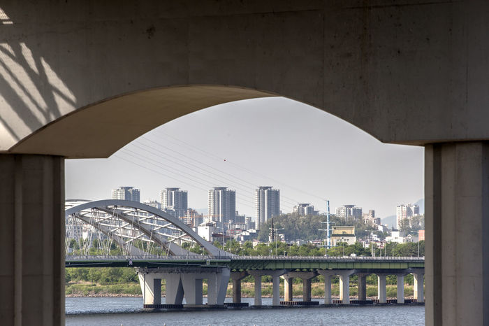 Arch Architecture Bridge Bridge - Man Made Structure Building Building Exterior Built Structure Capital Cities  City City Life Cityscape Connection Day Engineering Frame In Frame Modern No People Office Building Outdoors Residential District River Sky Tourism Travel Destinations Water