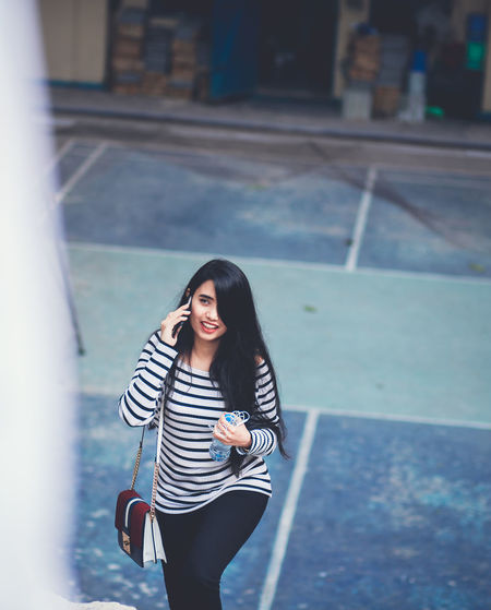 High Angle View Of Young Woman Talking On Phone While Walking On Steps