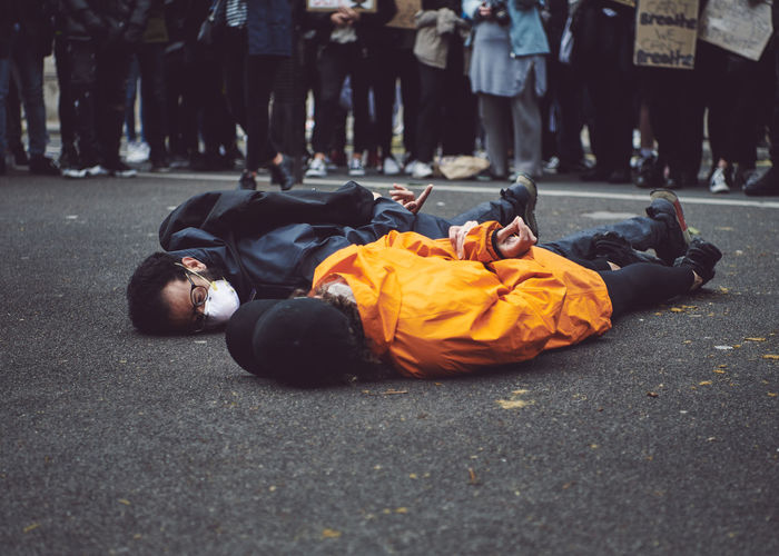 People lying on road in city