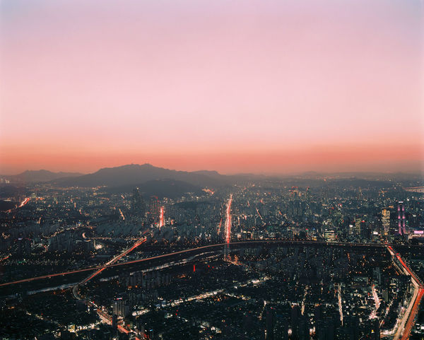 Red, pink, and purple hues blanket the sky as the sun sets in the South Korean capital of Seoul. Film Pink Seoul Aerial View Architecture Bridge - Man Made Structure Building Exterior Built Structure City Cityscape Connection Cosmopolitan Dynamic Highway Illuminated Metropolis Motorway Outdoors Pastel Sky Skyscraper Sunset Tourism Travel Destinations Vibrant