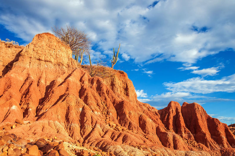 Dramatic red rock formation in Tatacoa Desert in Huila, Colombia Blue Colombia Desert Desolate Dry Heat Hills Hot Landscape Nature Neiva Outdoors Pillar Red Rock Sand Scenic Sky Stone Tatacoa Tourism Travel Valley View Wild