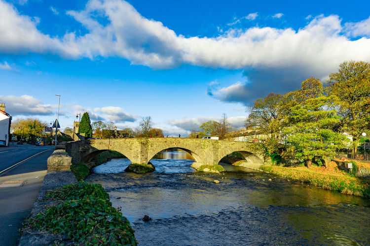 Cityscape of River Kent at Lound Road in Kendal, Cumbria, England in blue sky day Built Structure Water Architecture Cloud - Sky Sky Bridge Plant Connection Nature Bridge - Man Made Structure Tree Arch River Arch Bridge Day No People Transportation Reflection Building Exterior Outdoors
