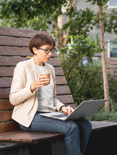 Freelance woman in park with laptop,cup of coffee. urban lifestyle of millennials. working remotely.