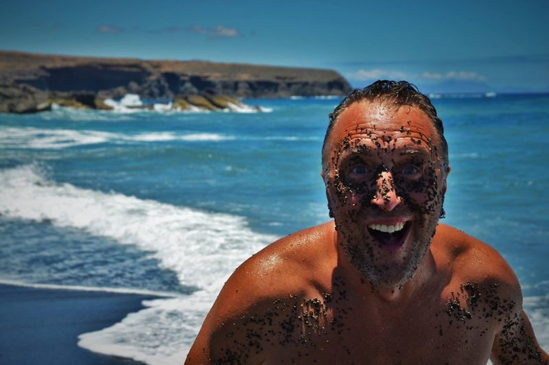 Portrait of cheerful man with mud on face standing at beach