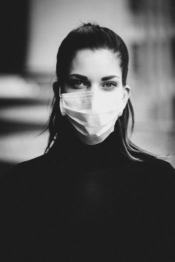 Close-up portrait of young woman wearing chirurgical mask.