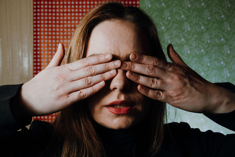 Close-up portrait of woman covering face with hand