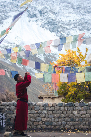 Side view of man standing by prayer flags during winter