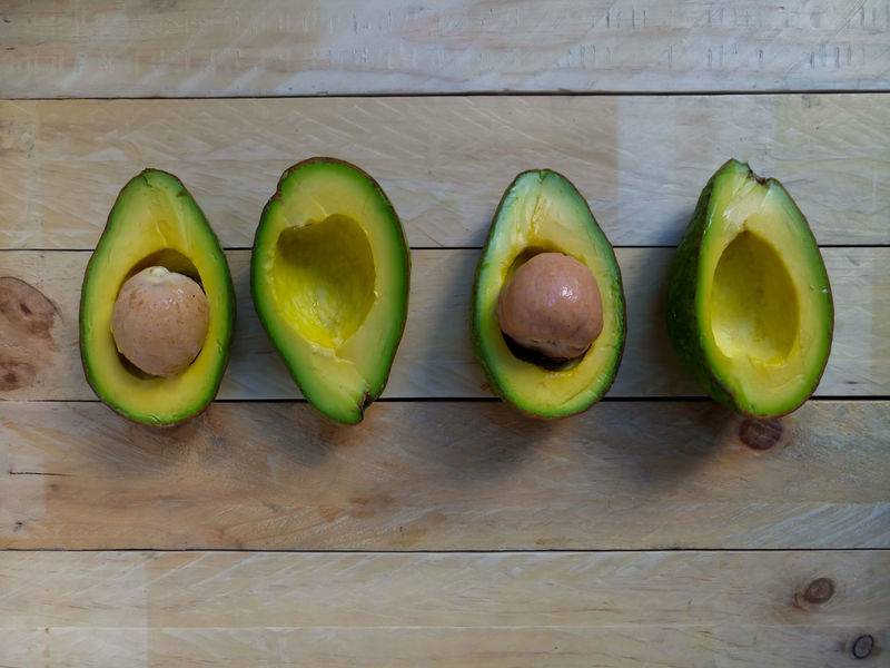 Avocados on wooden background Avocado Love ♥︎ Avocado Seed Avocado Avocado Ripe Close-up Day Delicious Food Food And Drink Food Health Freshness Fruit Green Color Healthy Eating Indoors  No People Ready-to-eat Ripe SLICE Still Life Table Tropical Fruit Wooden Background