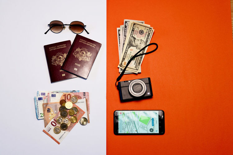 Sunglasses, smartphone, passports, camera and money on a white and orange paper background. Tourism concept. Dollar Money Cash Savings Banking Finance Bill Currency Wealth Background Banknote Bussiness Profit Green Close-up USD Exchange Loan  Paper Sign Payment Pay Stack Number Textured  Abstract Earnings Symbol Capital Assets Sunglasses Camera Phone Smart Phone Passports Passport Navigation Euro Coins Tourism Travel Concept Isolated Still Life Indoors  Studio Shot Directly Above No People Variation Large Group Of Objects Choice Arrangement Colored Background Technology Art And Craft Table Group Of Objects High Angle View Photography Themes Representation Orange Color Creativity Clock