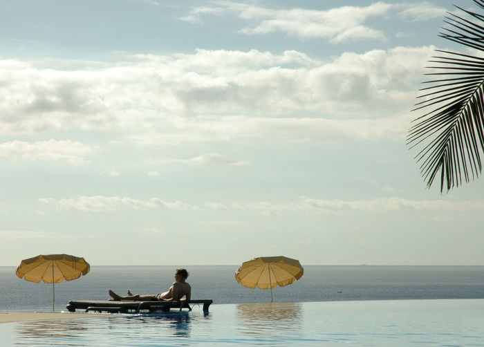 Man relaxing by sea at infinity pool