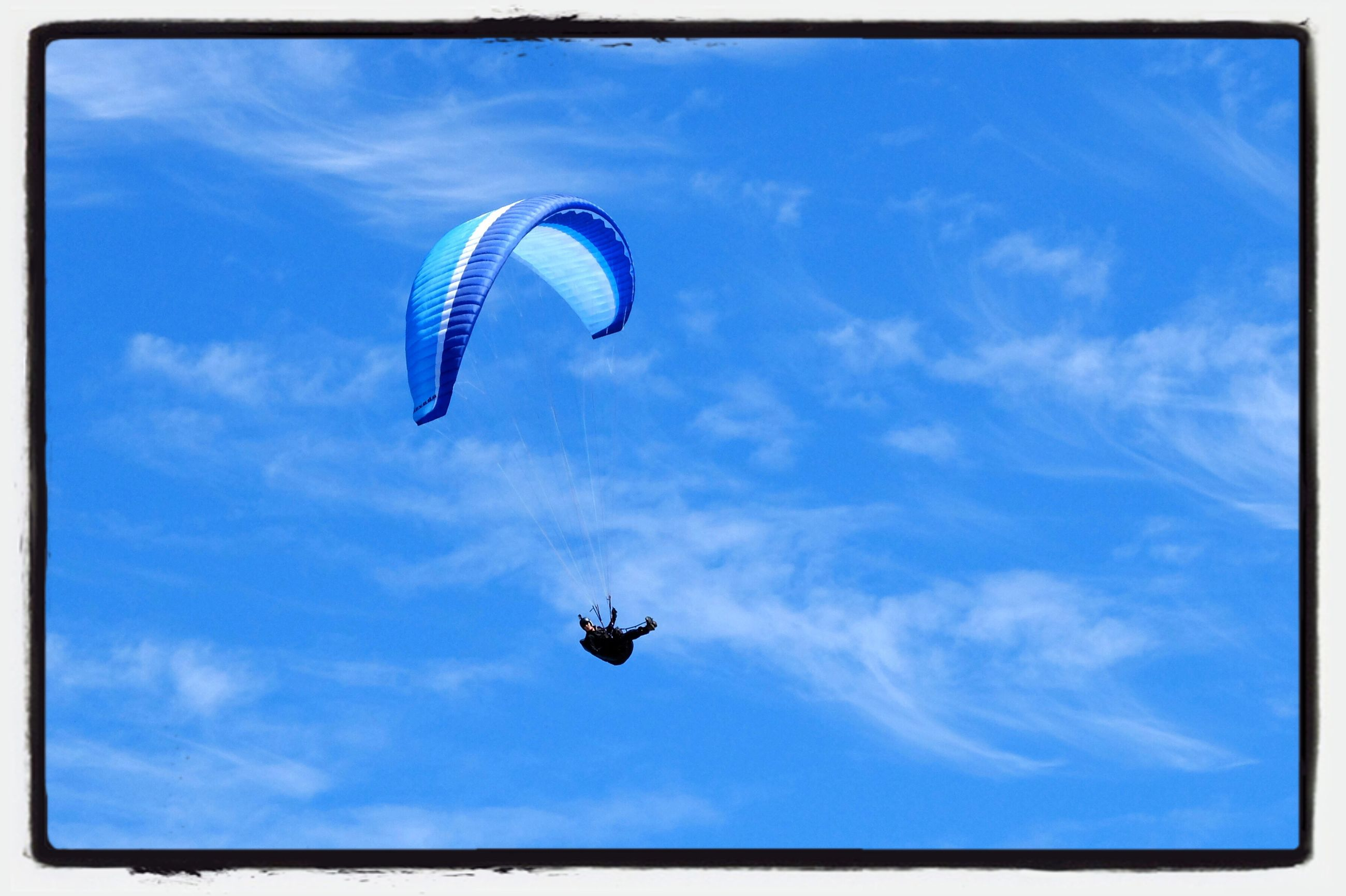 flying, mid-air, parachute, low angle view, extreme sports, blue, adventure, sky, transportation, paragliding, sport, leisure activity, exhilaration, cloud - sky, fun, freedom, motion, unrecognizable person