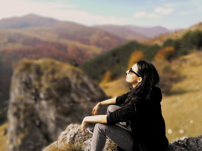 Young woman sitting on cliff against mountains