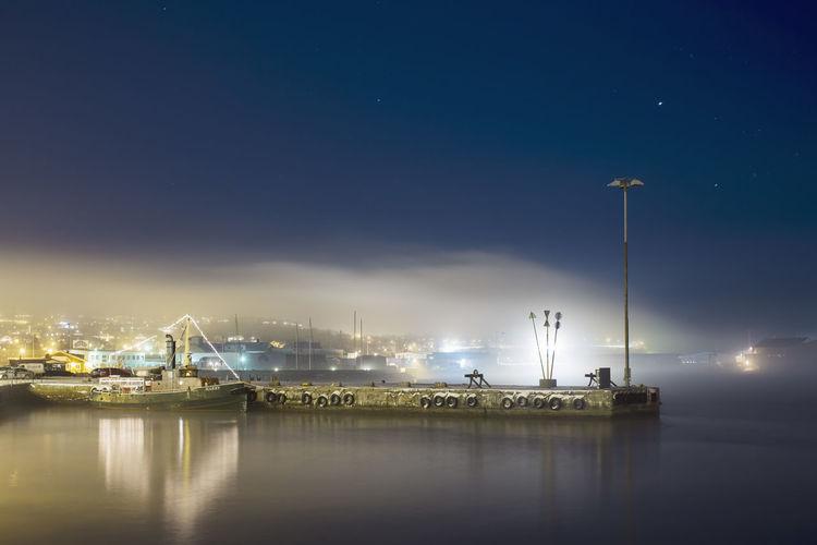 Sailboats moored at harbor against sky at night
