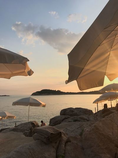 Parasols at beach against sky during sunset