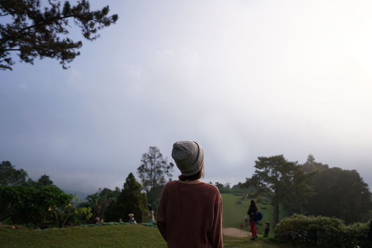 Young girl on peak of foggy mountain. Peaceful Refresh Holiday Tourist View Fog Treetop Outdoors Light Day Morning Travel Nature Light And Shadow Sunlight Mountain Young Women Countryside Freedom Life Sky Looking Tree Religion Rear View Sky Visiting