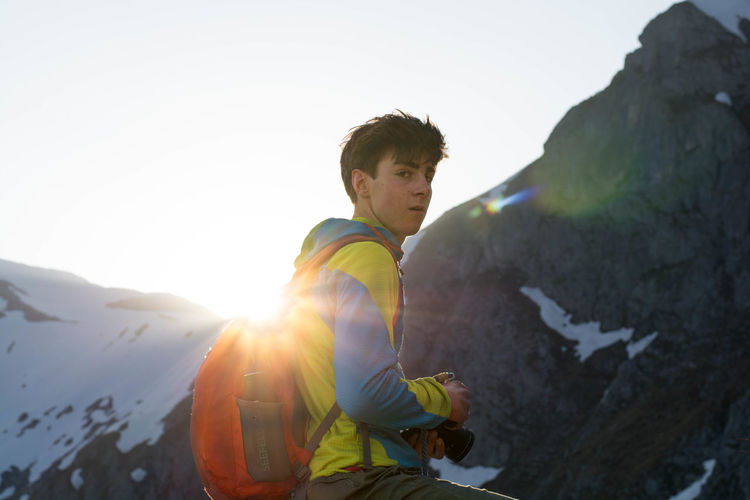 Side View Portrait Of Boy Wearing Backpack Against Mountain During Winter