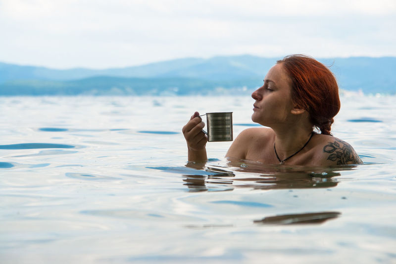 young female drink tea in water mountain landscape Outdoors Tea Relaxing Moments Relaxing Timez Lake Young Women Water Swimming Women Beauty Portrait Beautiful People Sea Beautiful Woman Milkshake Mojito Wet Hair