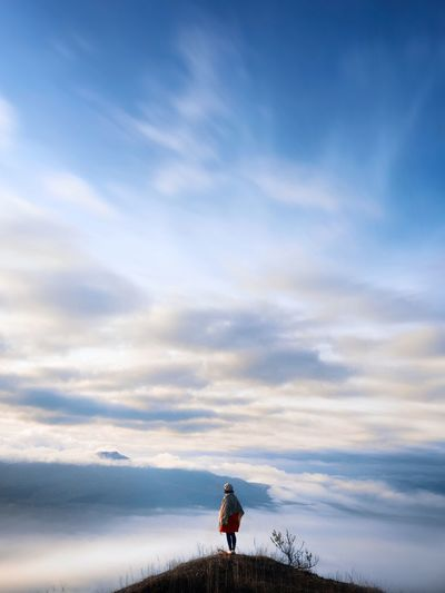 Woman Standing On Peak Against Sky