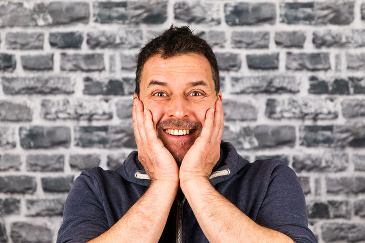 Portrait of smiling man against wall