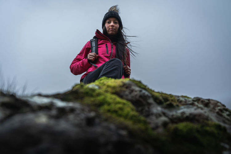 Portrait of woman standing on rock against sky