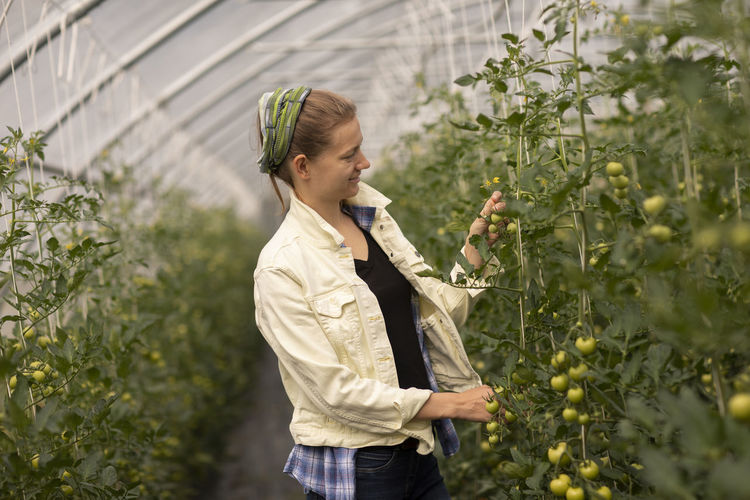 Young woman holding ice cream standing in greenhouse